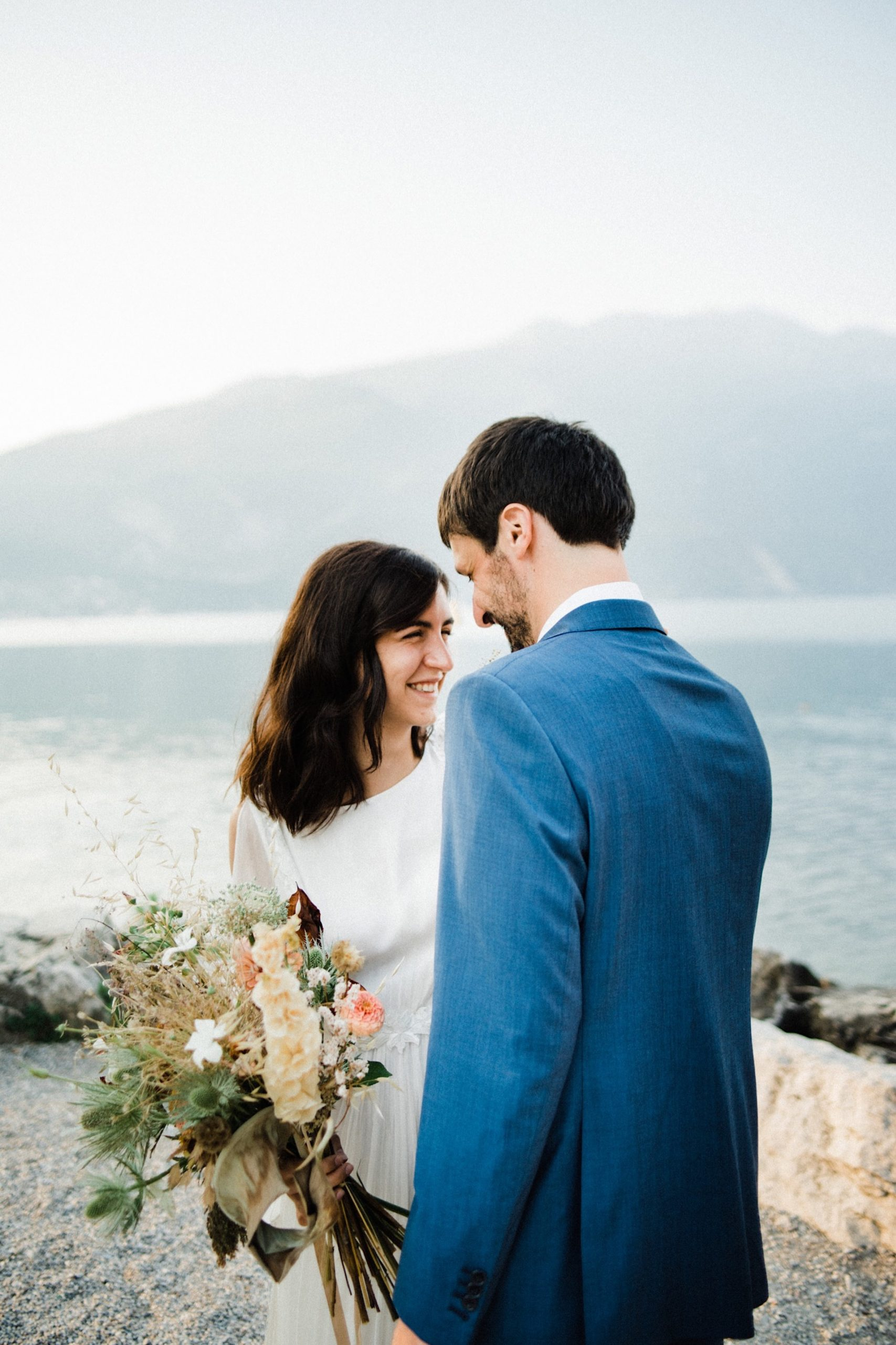 Portrait photo from a Boho Summer Elopement in Italy, featuring a mid-shot of a couple in sustainable wedding clothes smiling in front of Lake Garda.