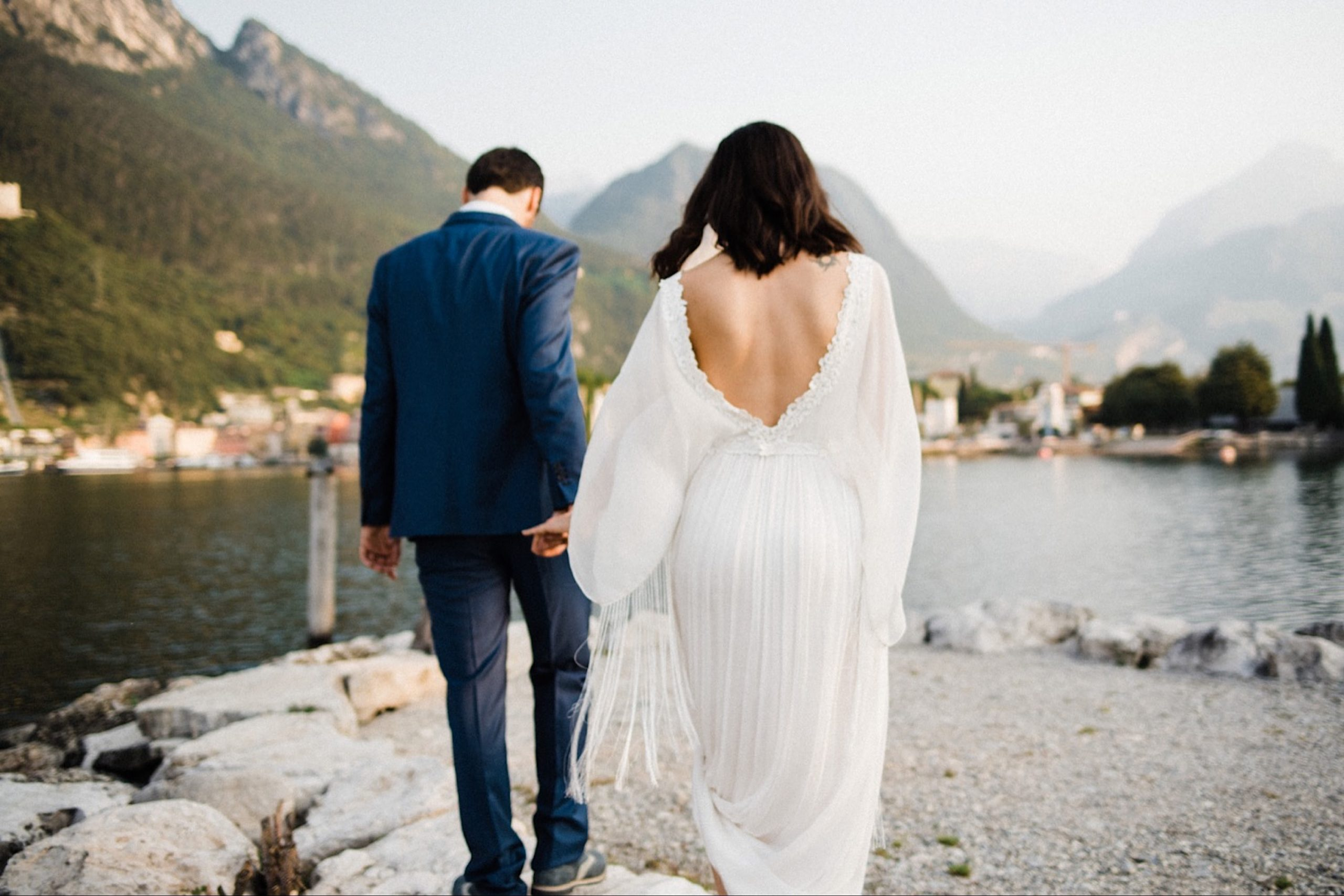 Romantic Boho Summer Elopement in Italy photo of a couple walking towards a lake with mountains in the background. The groom wears a blue May Faber Milano suit and the bride wears a backless, sustainable wedding gown by Leila Hafzi.