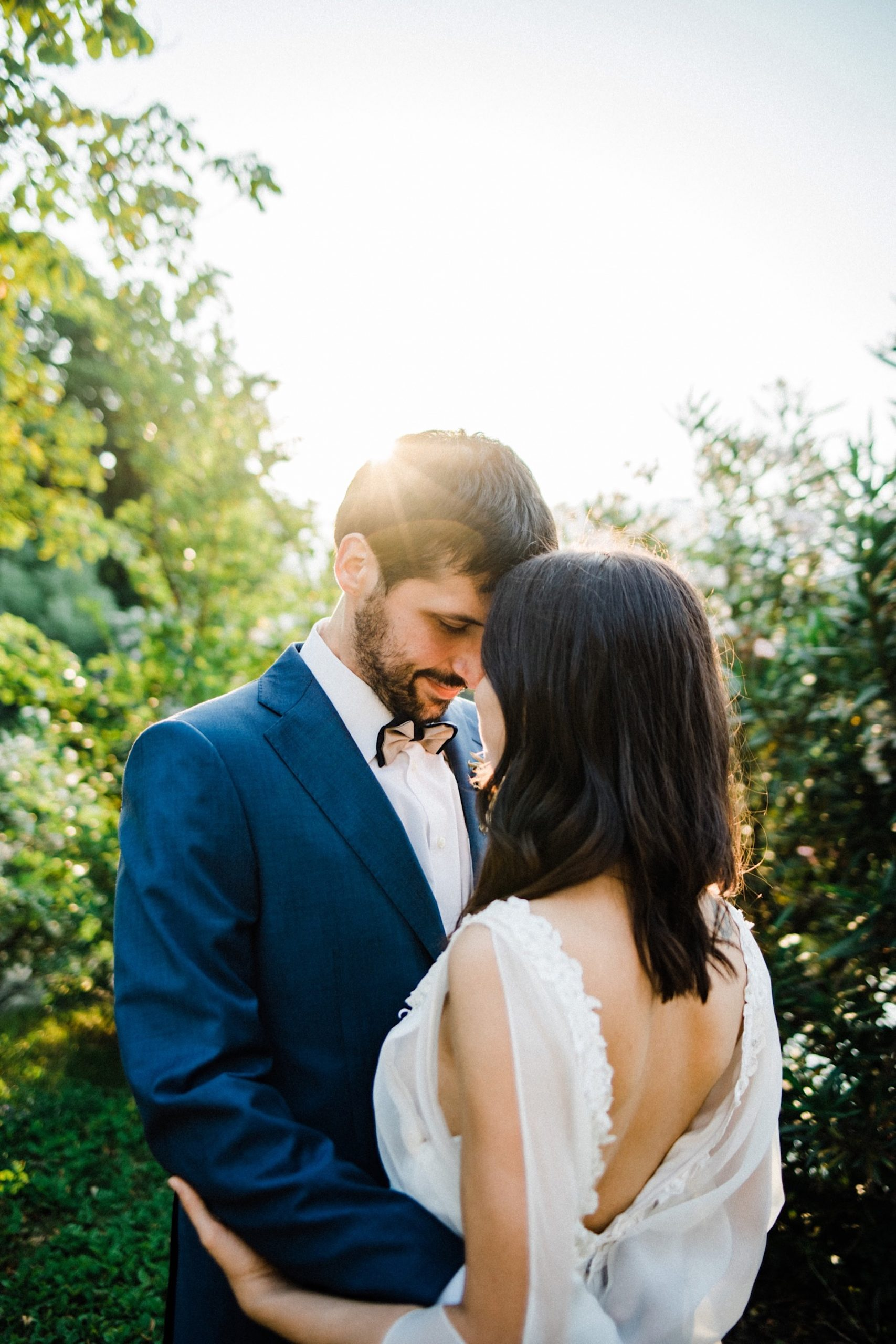 Beautiful, intimate elopement portrait of a couple embracing with their foreheads touching, taken by an Italian Elopement Photographer for their Boho Summer Elopement in Italy.