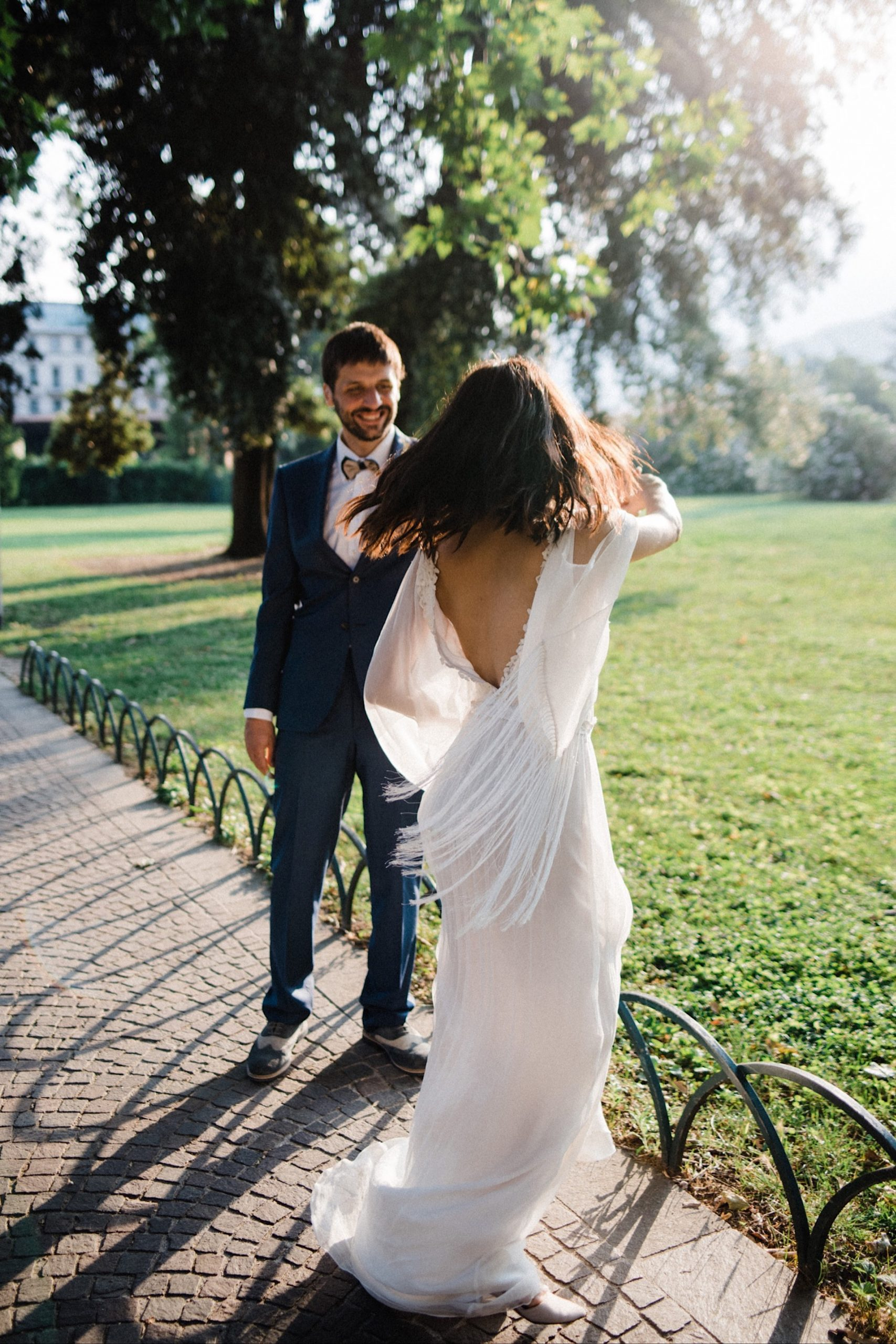 Photo of a Boho Summer Elopement in Italy as the groom spins the bride around. Her sustainable bridal gown, which has tasseled sleeves, moves beautifully around her.