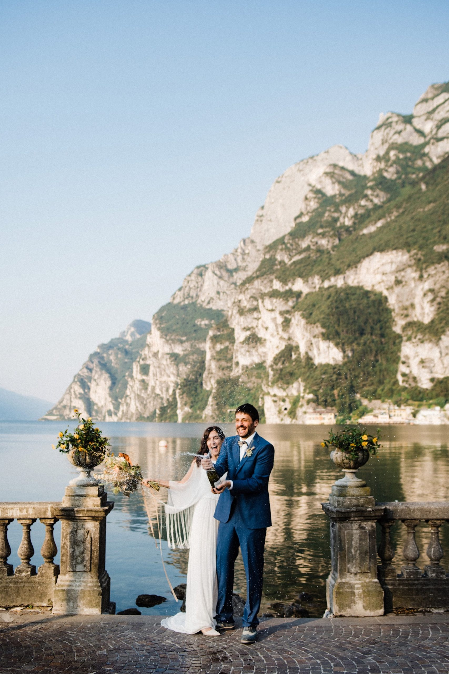 A couple pop open a bottle of Prosecco to celebrate their elopement in Italy. In the background, you can see Lake Garda and one of its surrounding mountains.