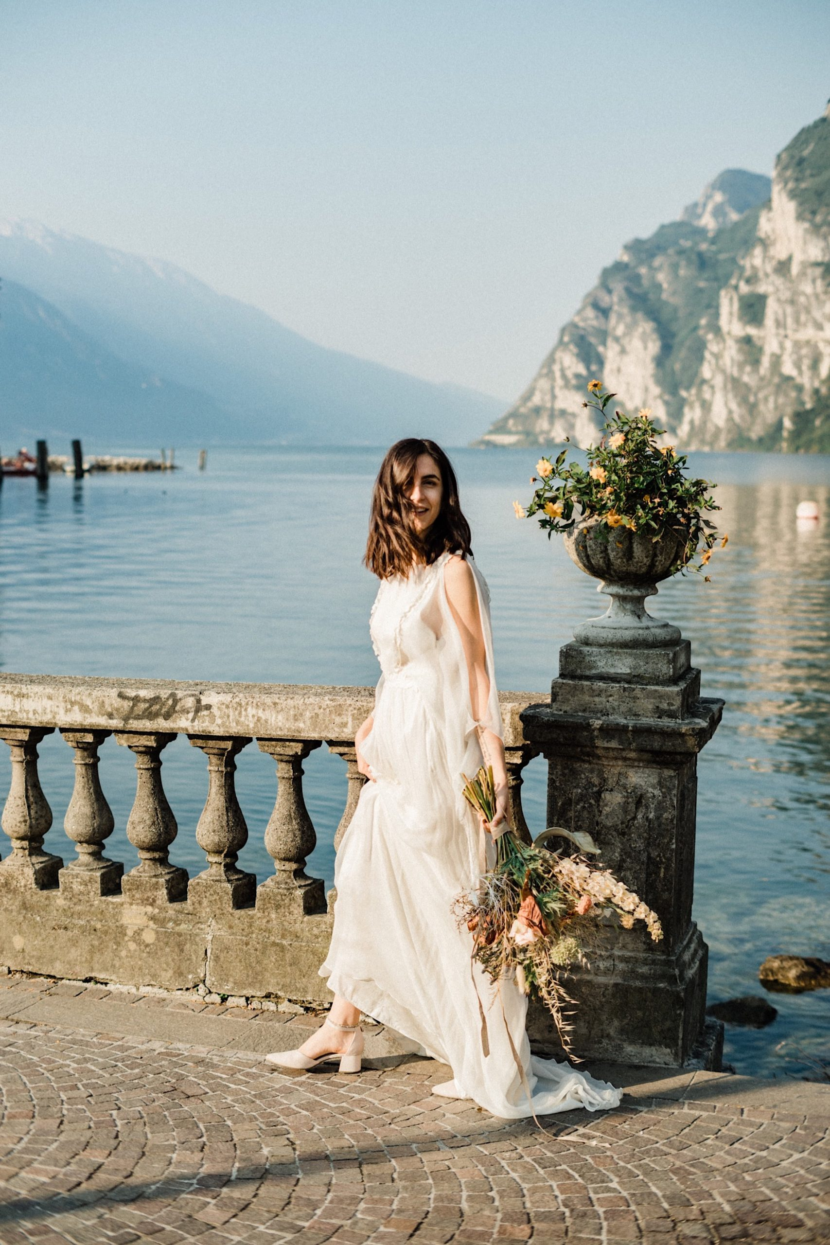 A wide photo of a newly married bride walking and smiling in front of Lake Garda, carrying a beautiful bouquet of dried and fresh flowers/