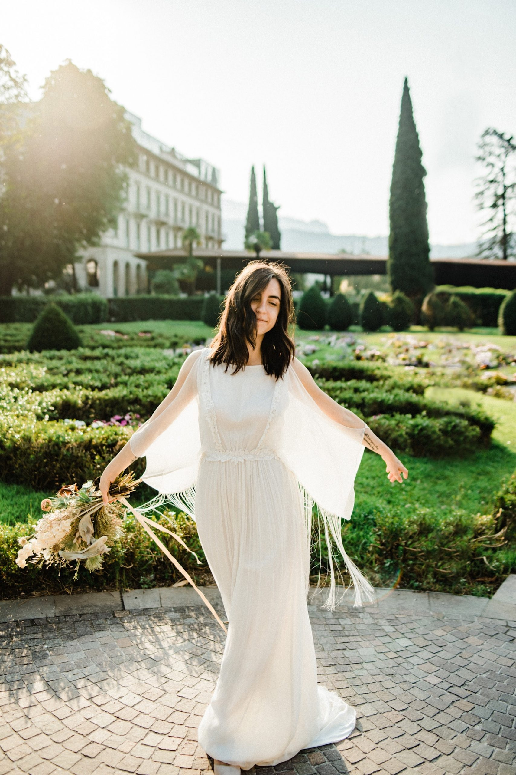 Italian Elopement Photography of a bride twirling around in front of some curated Italian gardens.