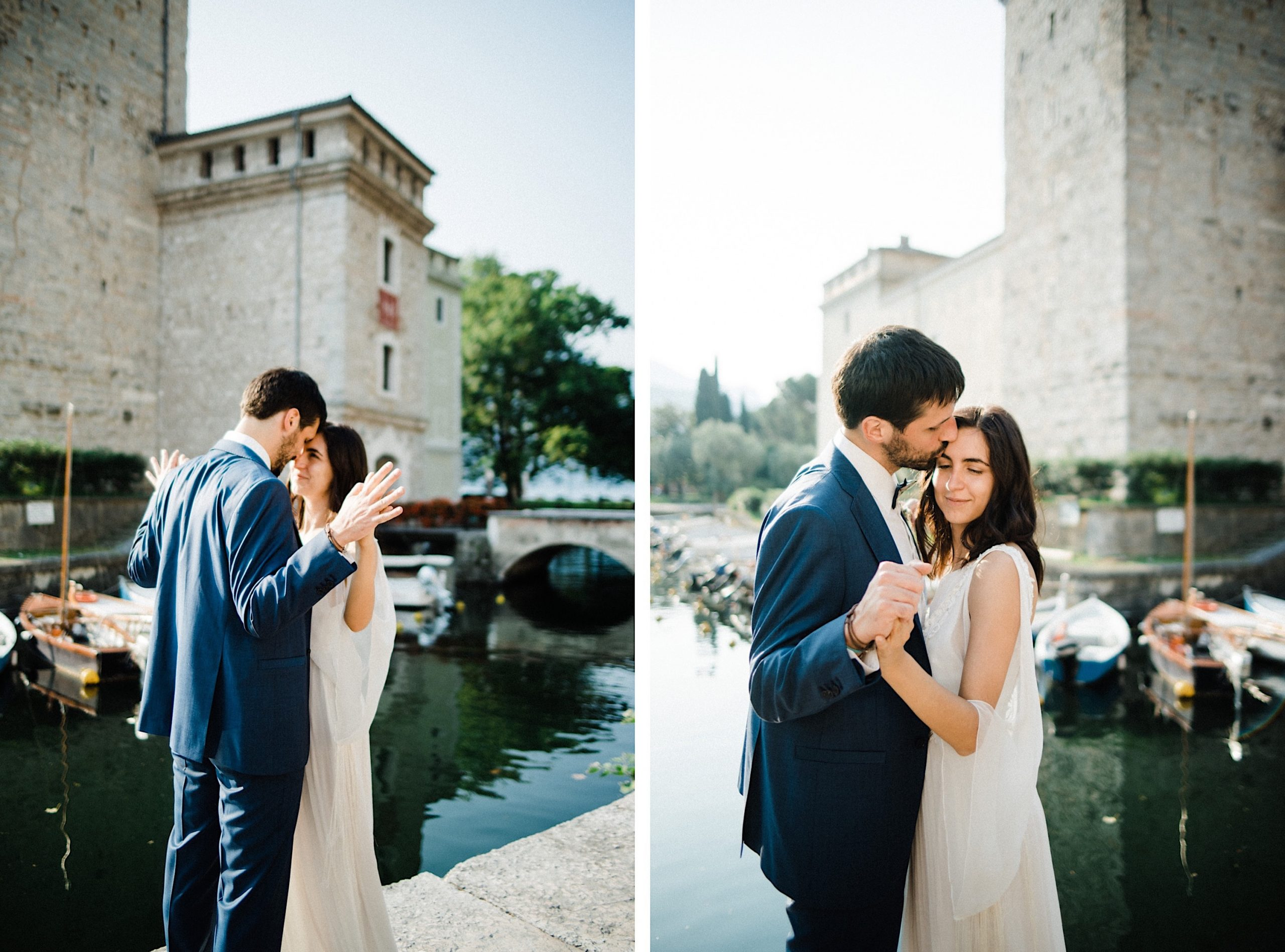 A newly married couple standing together in front of an old Italian castle by the lake, cuddling and kissing.
