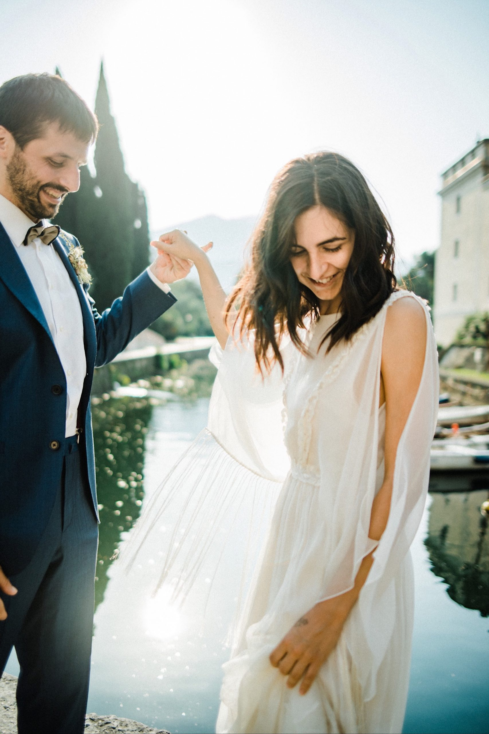 A medium shot of a bride looking down smiling, while her groom smiles at her, taken by an Italian Elopement Photographer for a Boho Summer Elopement in Italy.