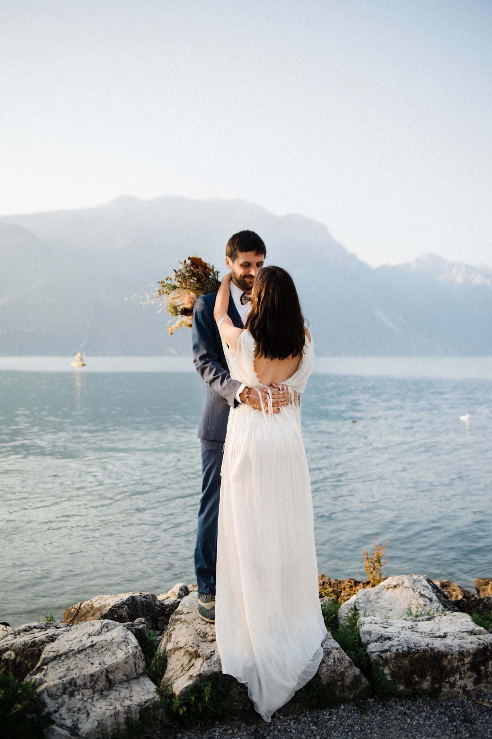 Wide shot of a newly marrried couple hugging and smiling, the bride has her back to the camera and is looking out over Lake Garda, photo by an Italian Elopement Photographer.