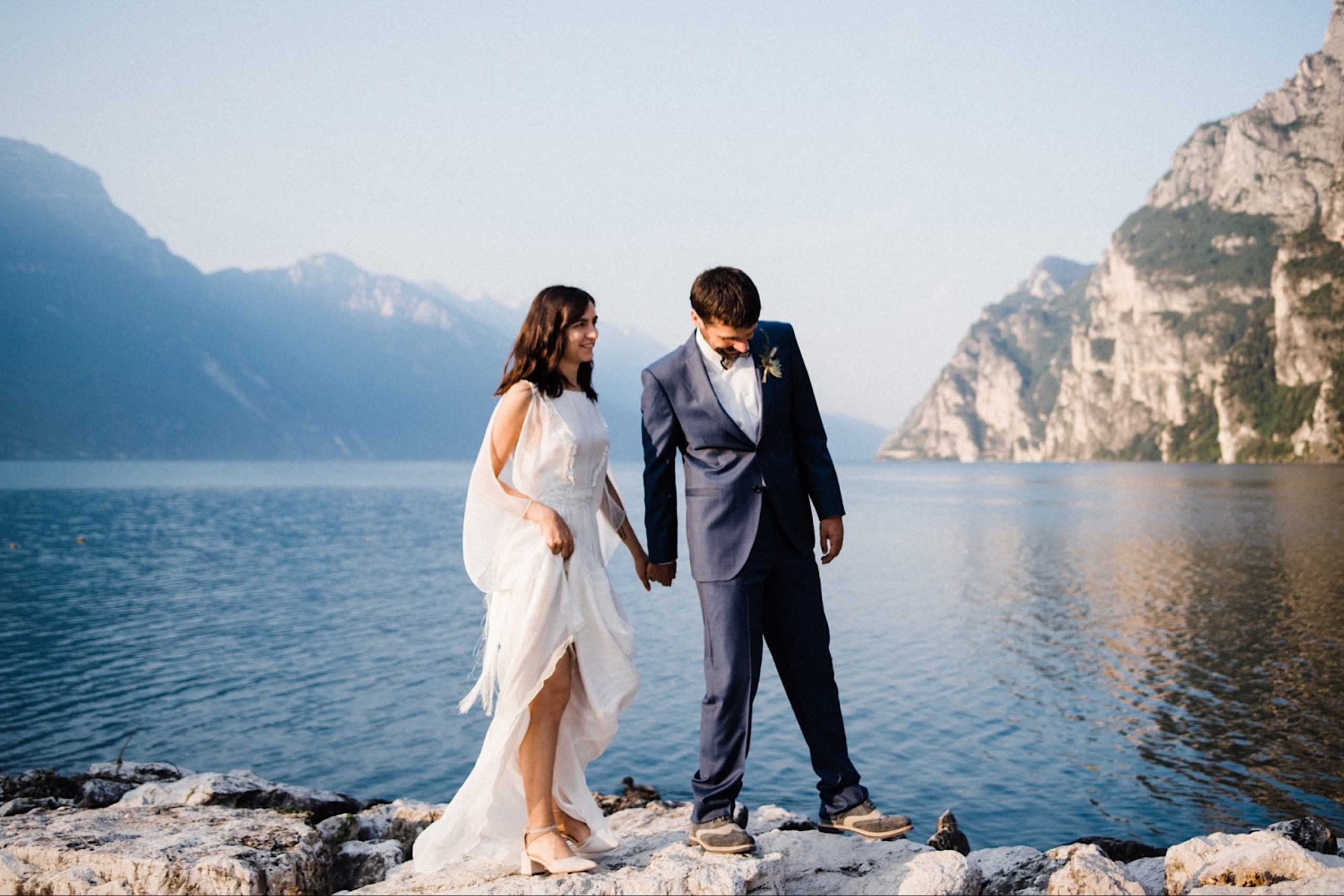 A wide shot by a Candid Italian Elopement Photographer of a newly married couple walking along rocks by the side of Lake Garda, with mountains in the background.