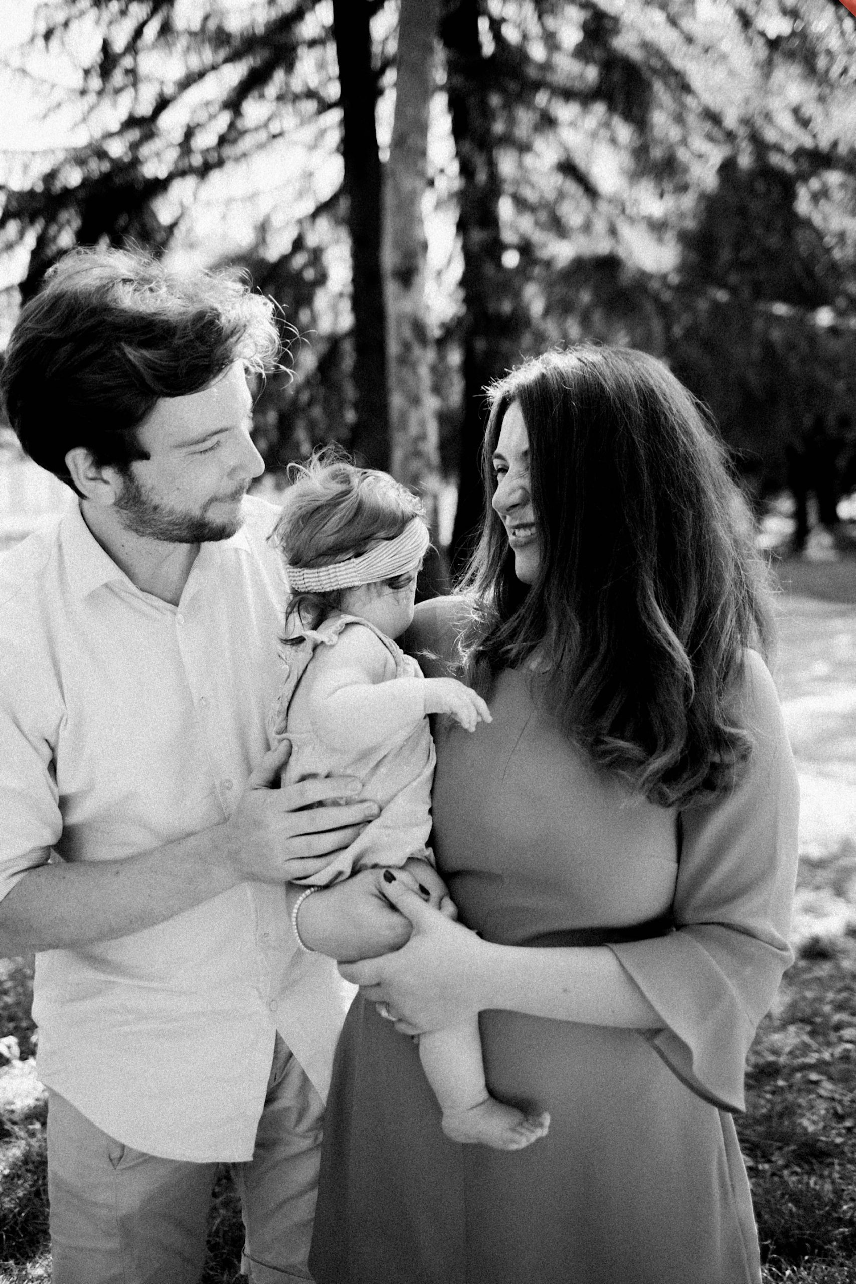 Black & white relaxed family photography of young parents holding their baby daughter between them, both of them looking at her.