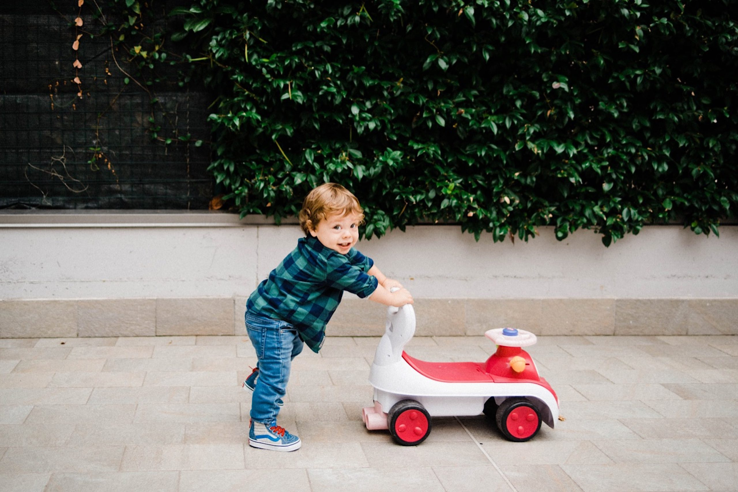 Fun Milan Family Portraits of a toddler walking a car toy and smiling.