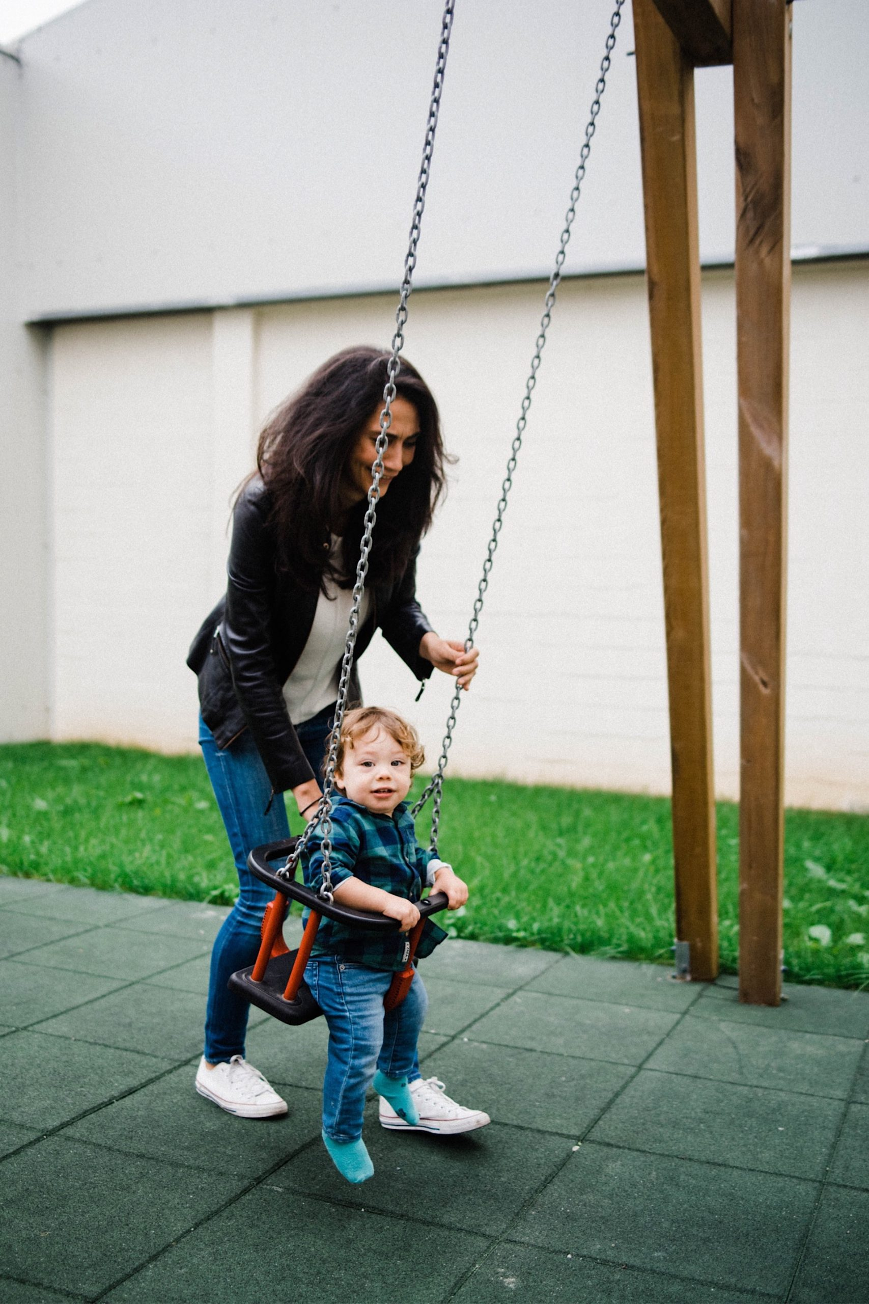 Portrait photo of a Mum pushing her toddler on a swing, at their local playground.