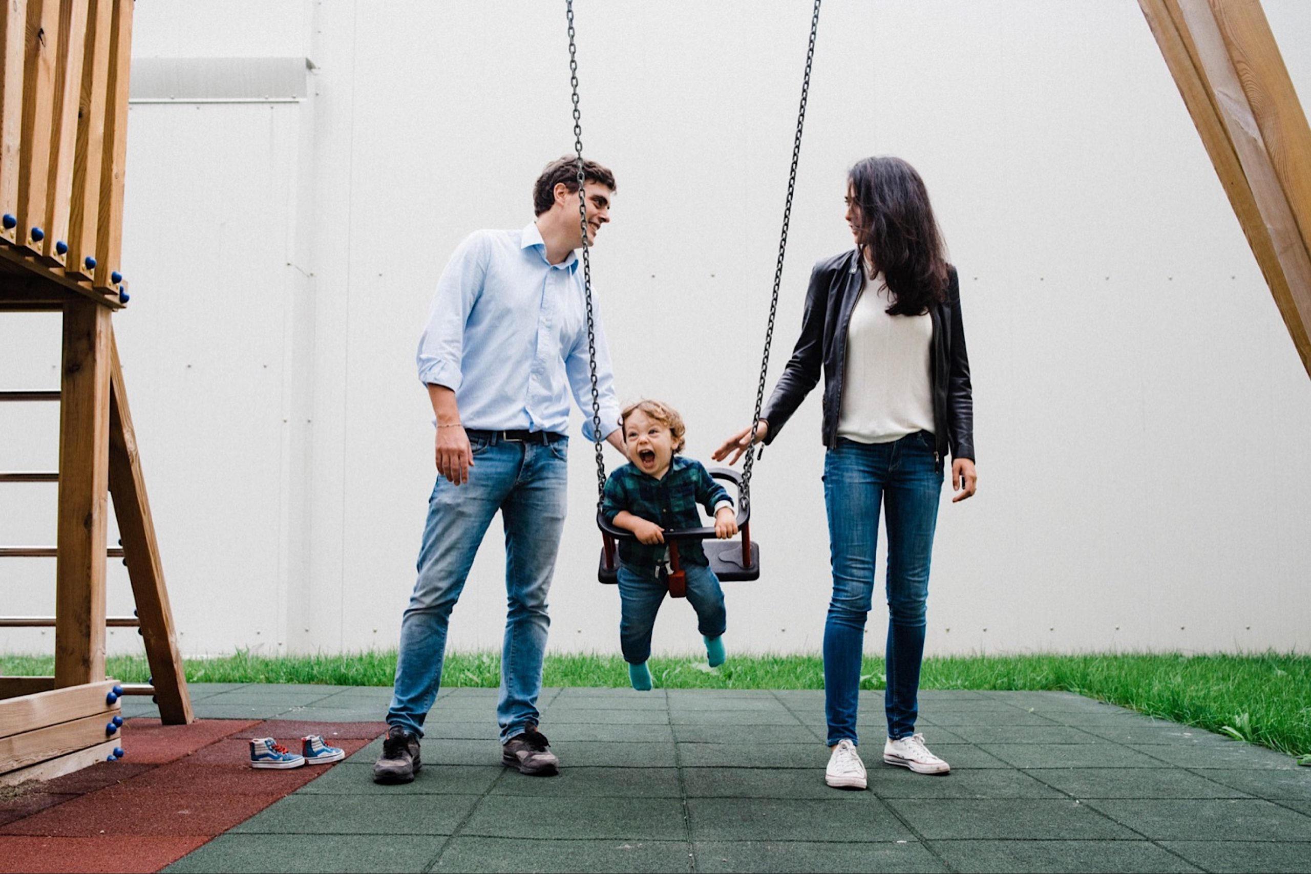 A photo of a Mum & Dad pushing their baby boy on the swing as he laughs during their Fun Milan Family Portraits.