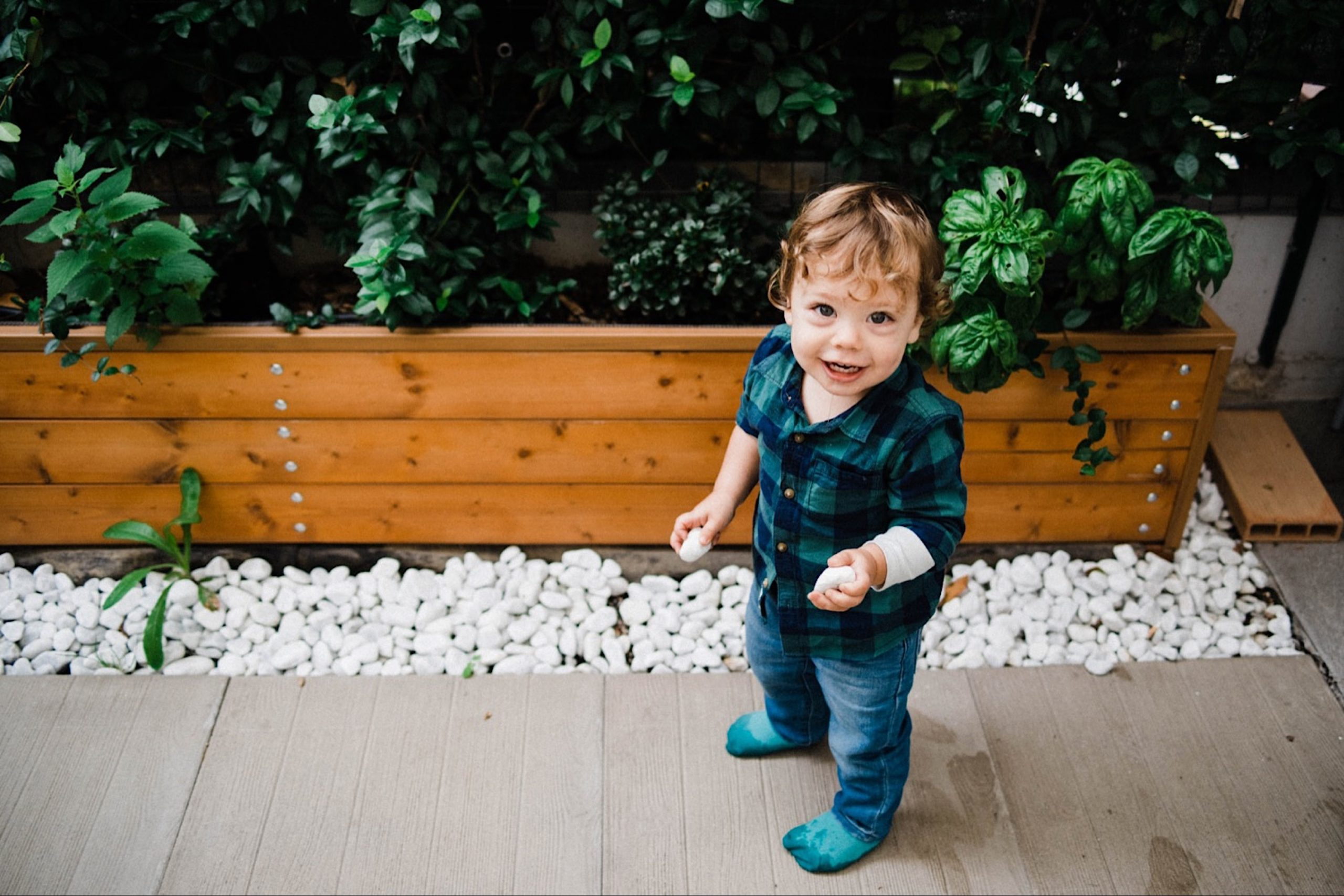In-Home Family Photography in Milan of a toddler holding pebbles from his garden and smiling.