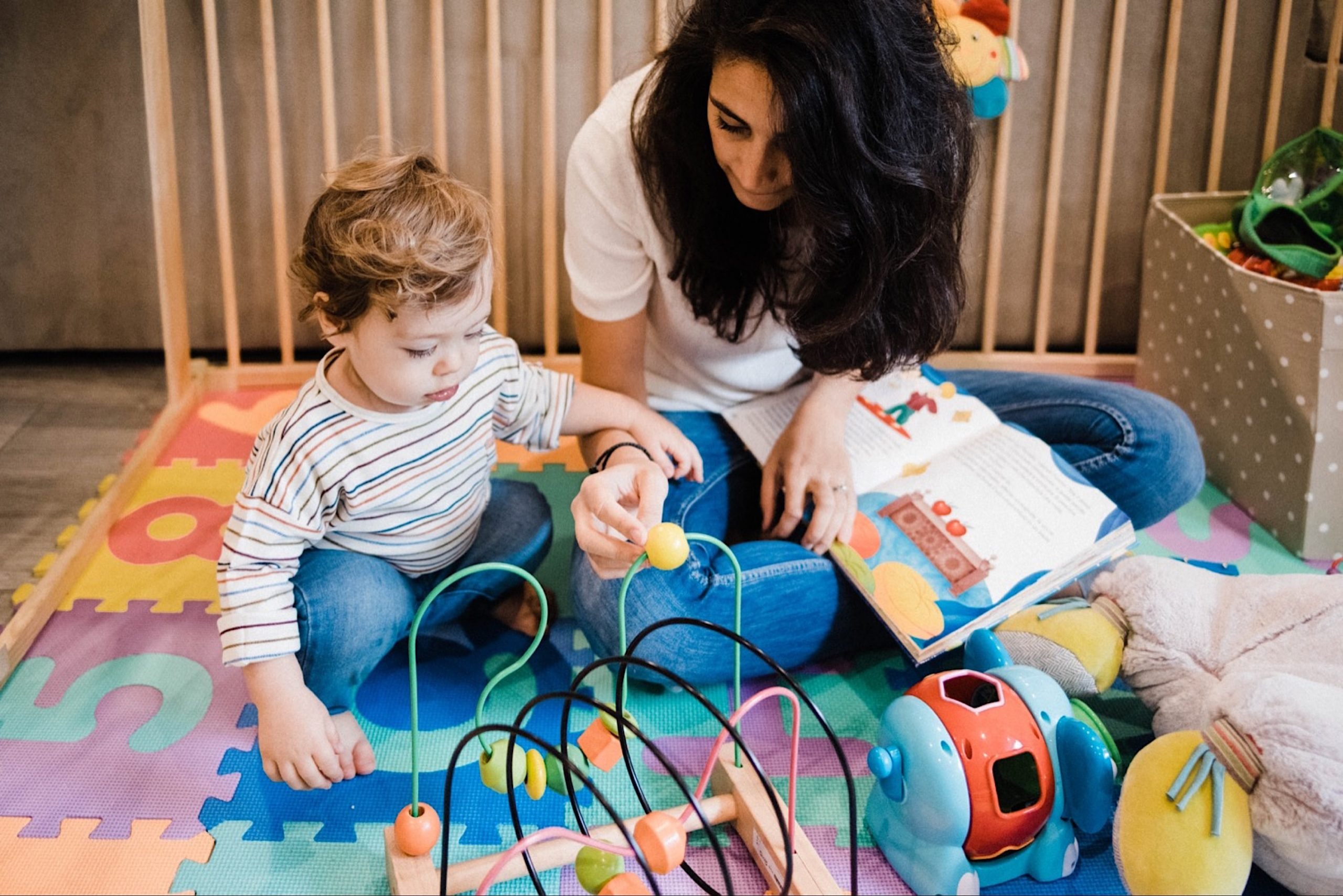 In-Home Family Photography of a Mum playing on a colourful abacus toy with her toddler.
