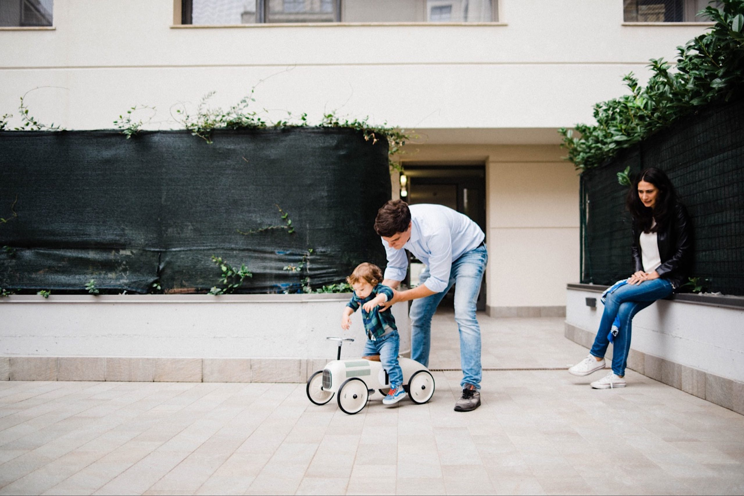 A Dad plays with his baby boy on a toy bike while his Mum watches on.