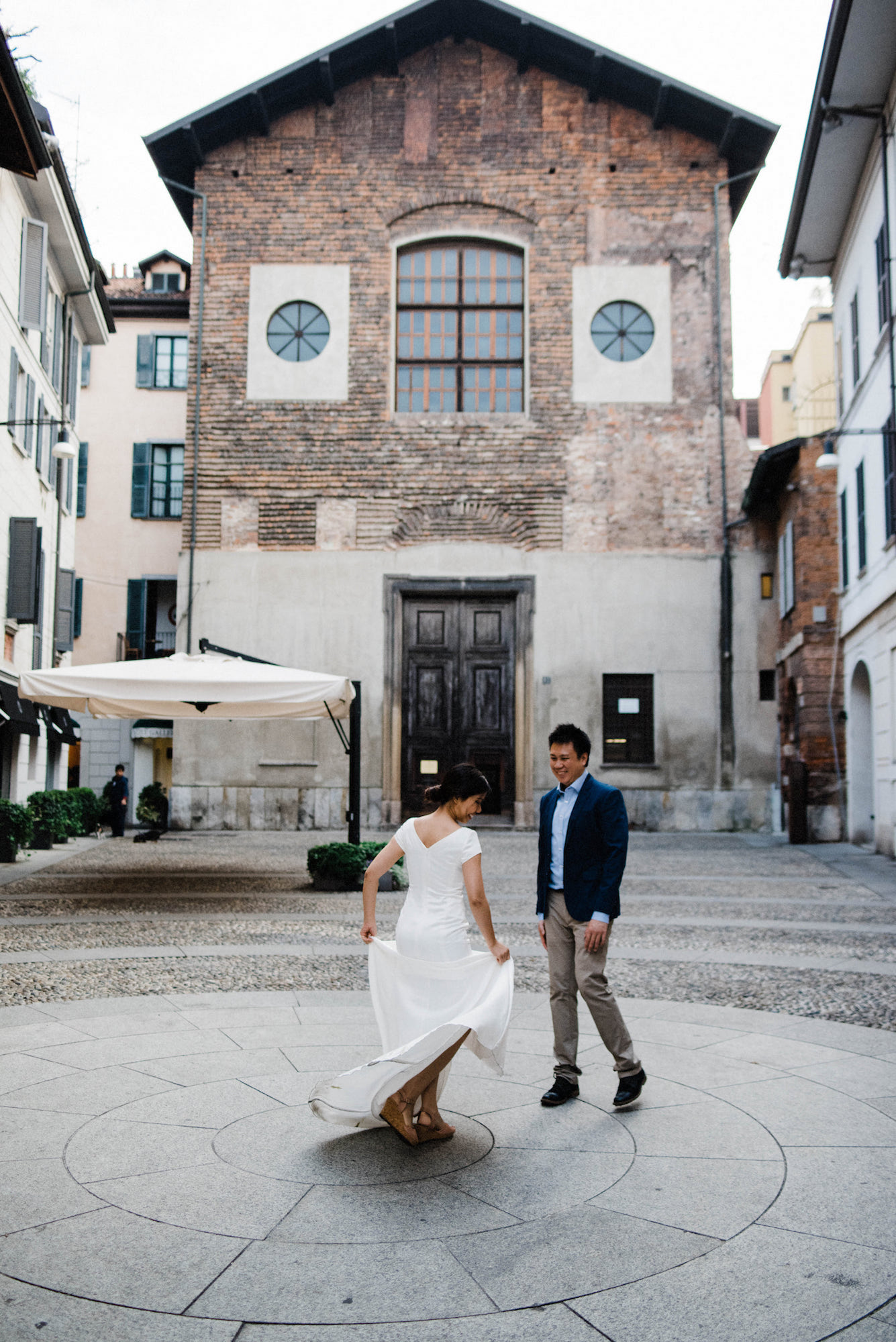 A portrait-oriented photo of a couple dancing in a square during their Italian Elopement in Milan.