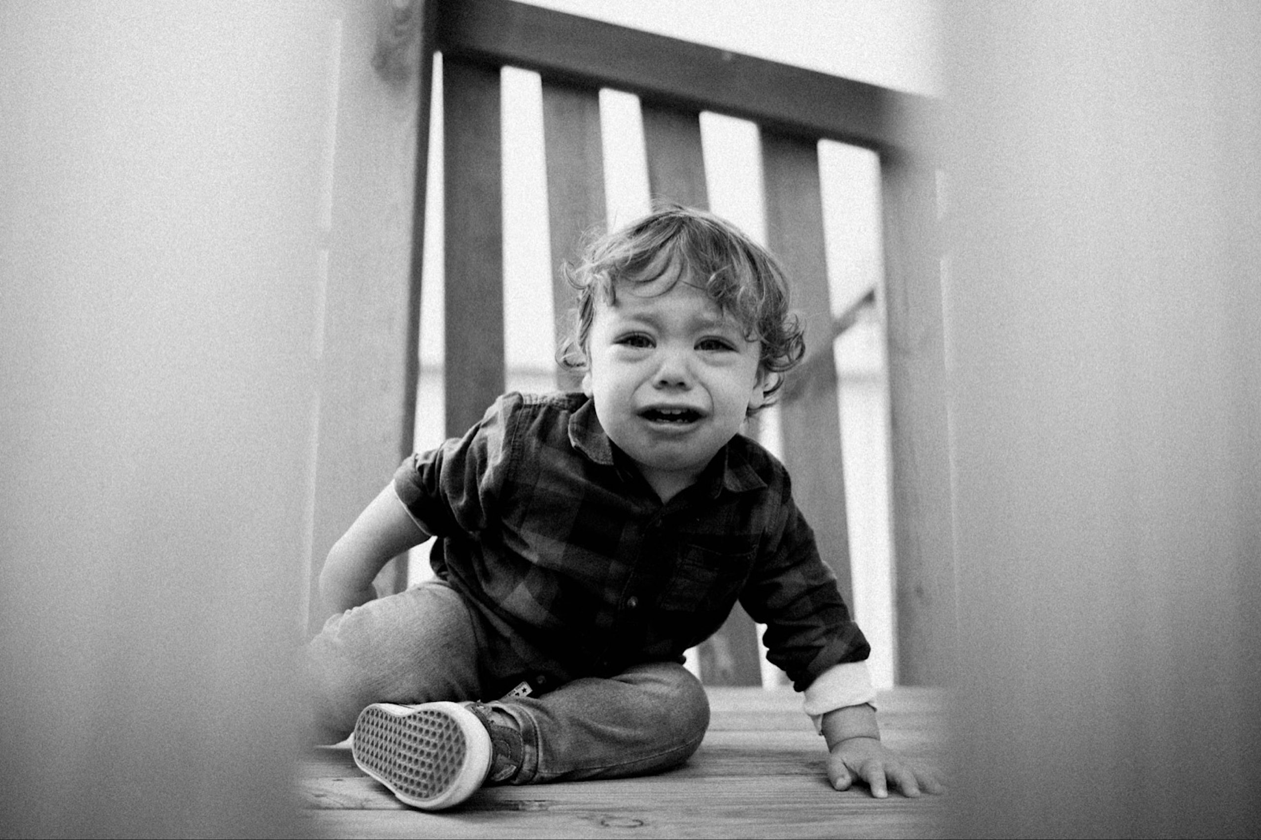 A black & white photo taken through the wall of a playground platform, he's looking at the platform and crying because he wants to go on the swing.